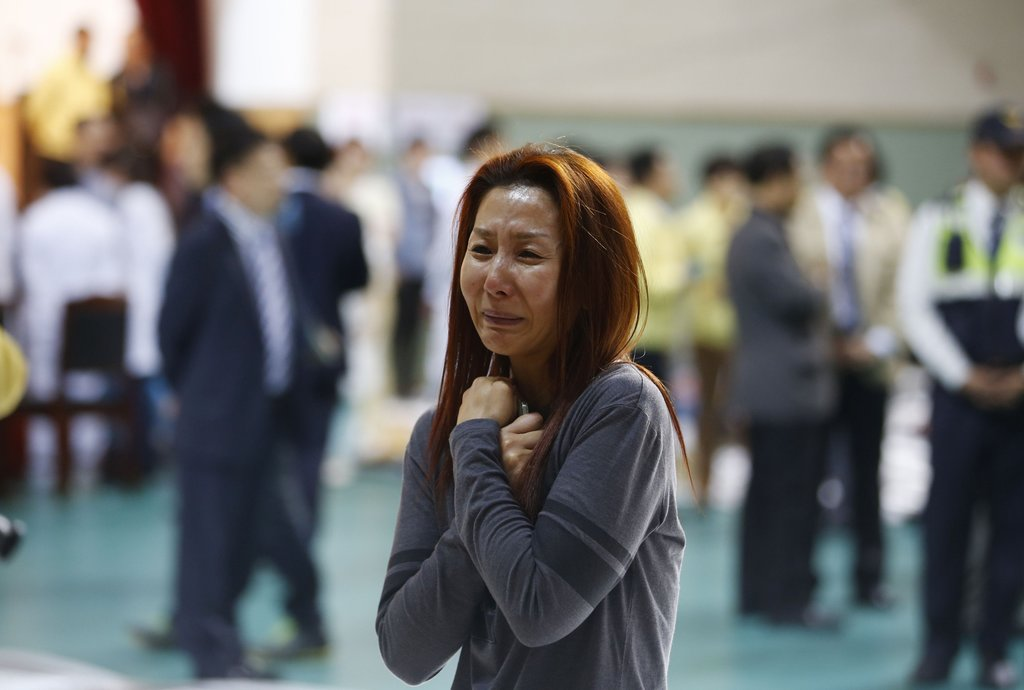 The mother of a passenger who was on a sinking ferry reacts as she finds his son at a gym where rescued passengers gather in Jindo