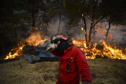 A firefighter rubs his face during a wildfire in Caramulo, central Po