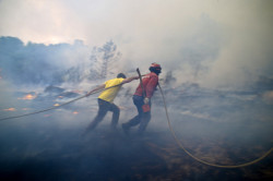 A local and a firefighter try to putout a wildfire in Caramulo, centr