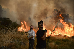 Locals shout as they try to extinguish a wildfire in Caramulo, centra