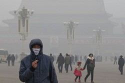 A man wears a mask on Tiananmen Square in thick haze in Beijing Tuesd